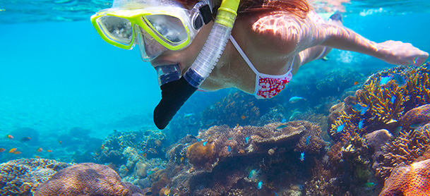 A girl with snorkeling equipment swims over a reef