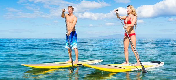 A man and woman each stand on paddleboards in open water