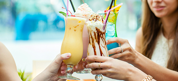Four tropical beverages are raised together as a toast