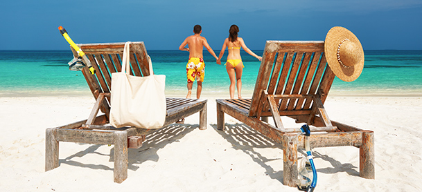 A couple holding hands and walking towards the water, leaving two wooden beach chairs in the foreground