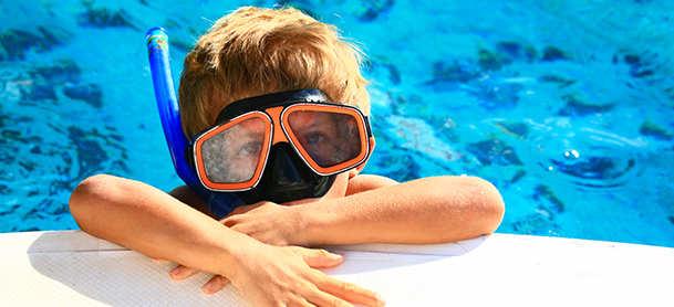 Kid in snorkle and mask relaxing half out of the water