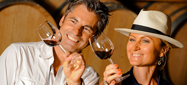 Woman in hat and man looking at their glasses of wine