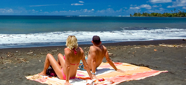 Man and woman sitting on beach towels near the ocean