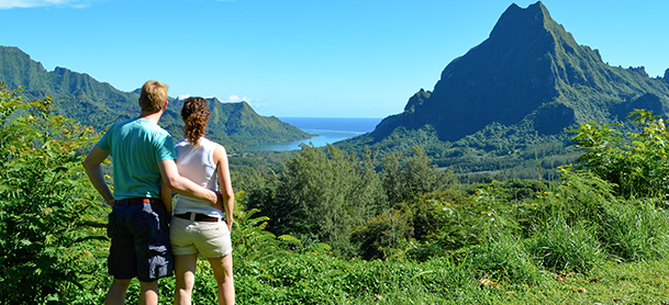 Man with arm around woman as they view green mountain