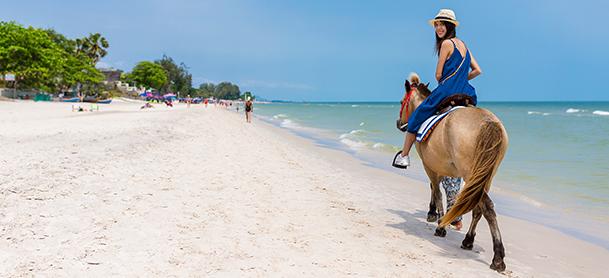 Woman riding horse on beach