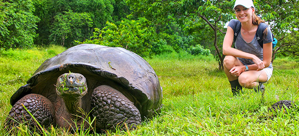Woman near giant tortoise
