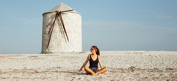 Woman sitting with crossed legs in sand