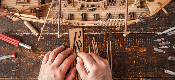 close up of hands working on boat model