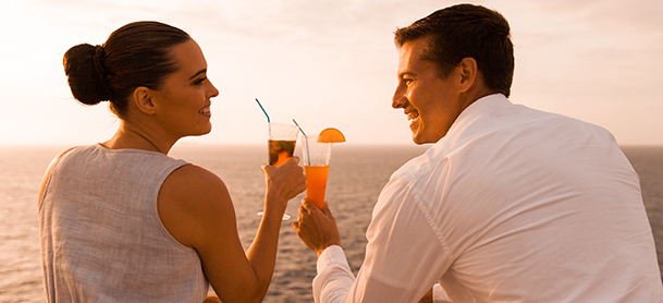 Couple dressed in white toasting a drink nearing sunset