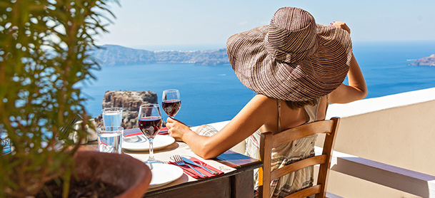 Woman in hat enjoying glass of wine overlooking water