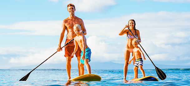 Family paddleboarding. Dad with one child. Mom with another.