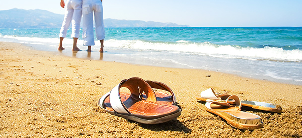 Sandals left on beach as people in white pants walk along beach