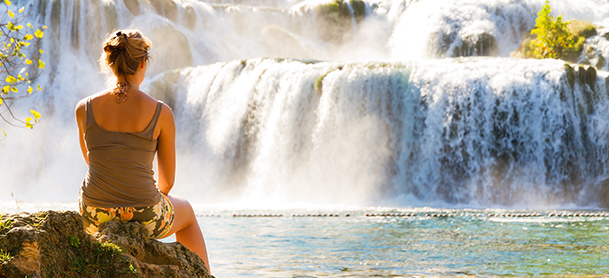 Woman sitting on rock in front of waterfalls
