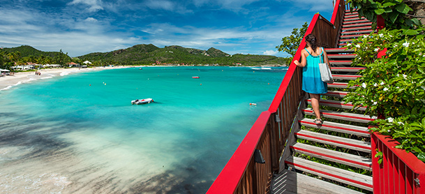 Woman on red staircase overlooking beach and blue water