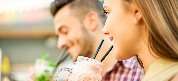 Man and woman enjoying cold drink in a jar using straws