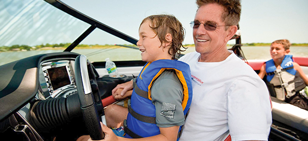 Boy on dad's lap steering yacht