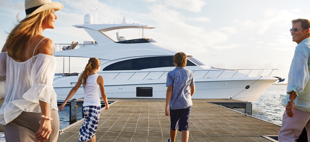 A mother and father with two young kids walk along a dock toward a yacht