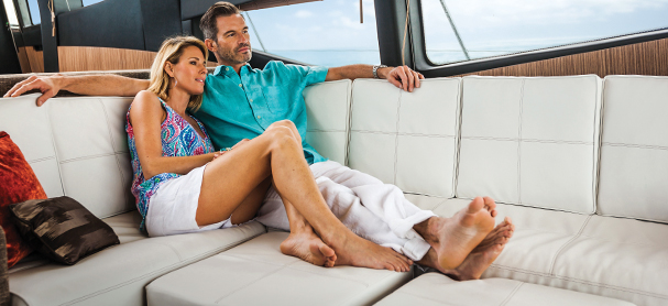 A couple sit on a sofa on a boat