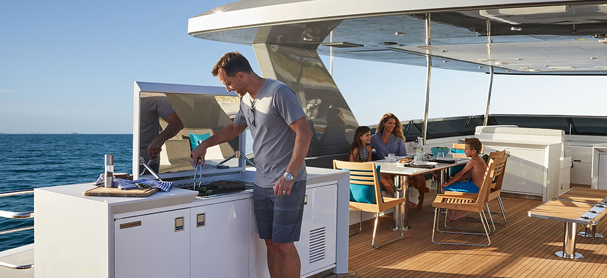 A man grilling meat while standing on the flybridge of a yacht