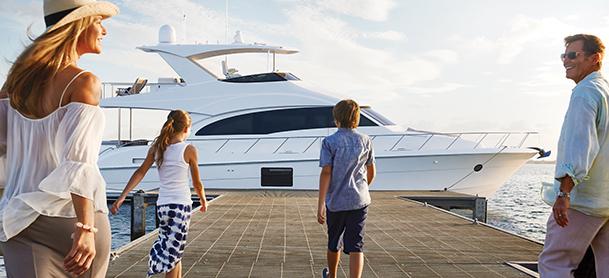 Family walking on dock towards yacht