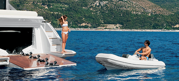 Man aboard smaller watercraft as woman watches from yacht