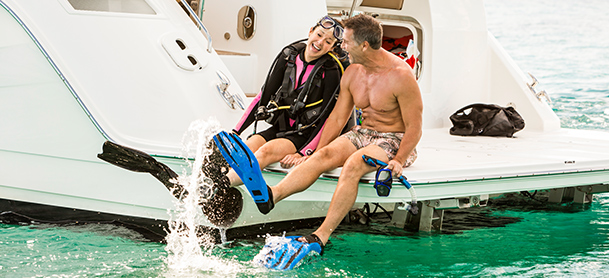 couple wearing scuba gear sitting on the swim platform of a yacht