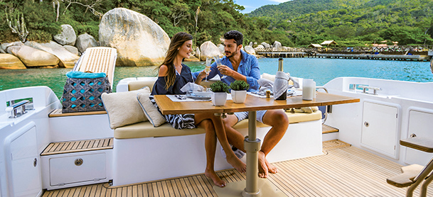 couple sitting at table on the aft deck of a yacht