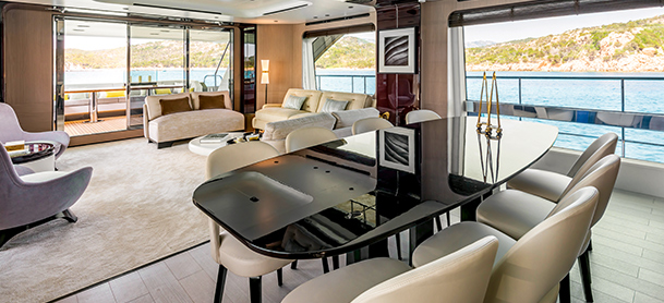 chairs around a table on board a yacht with water in the background