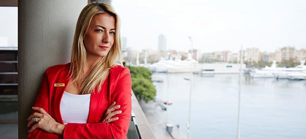 professional woman with arms crossed overlooking water