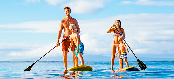 family on stand up paddle boards on open water