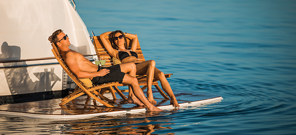 couple sitting on chairs on the swim platform of a yacht