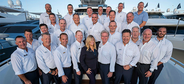 group of yacht team professionals in uniform standing on bow