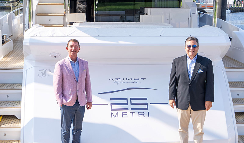 two yacht salesmen standing on a dock in front of an azimut grande 25 metri