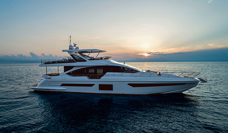 a profile view of an azimut grande 25 metri in open water as the sun sets behind it