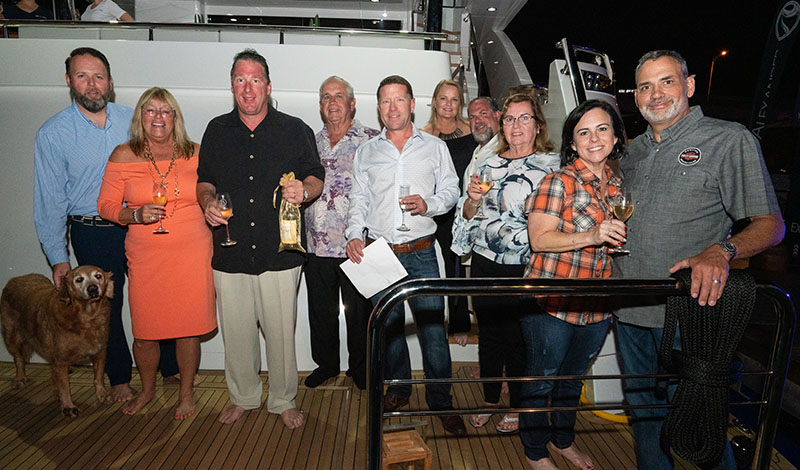 A group of people in front of a yacht