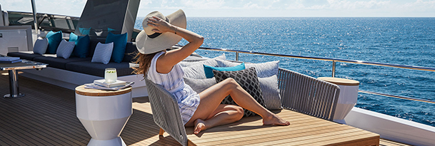 woman holding on to her sunhat and she sits aboard yacht