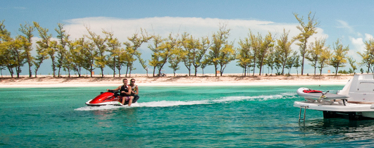 People riding jet ski by shore lined with trees
