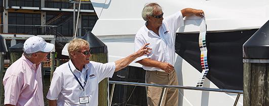 Three men looking at colors samples against an Ocean Alexander yacht