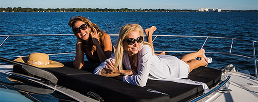 Two ladies laying on the bow of a Sea Ray Fly 510