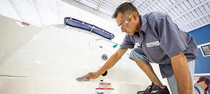 man in uniform polishing yacht deck