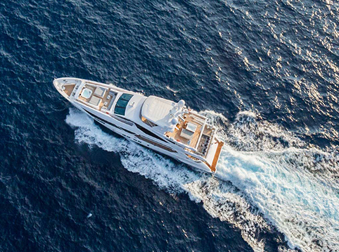 Overhead view of a large white Benetti yacht on open ocean