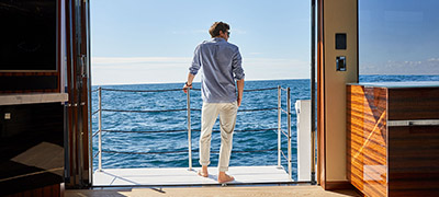 man standing on side deck of yacht looking out to open ocean