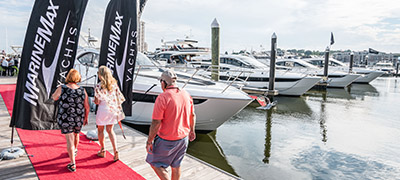 people walking down dock on red carpet with MarineMax Yachts flags flying as yachts are lined up