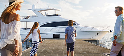 family walking down dock towards a yacht