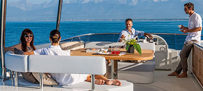 group of people relaxing, eating, and drinking on deck of a yacht