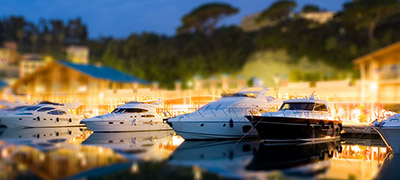 several yachts lined up along dock with lights on at sunset