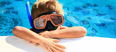 little kids with large goggles and snorkel on in the water