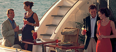 two couples with cocktails and appetizers on the aft deck of a yacht