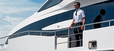 man in uniform standing on side deck of yacht