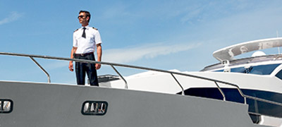 uniformed man standing on the bow of a yacht